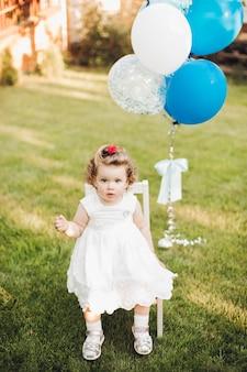 Linda garotinha caucasiana com cabelo curto ondulado e louro, num vestido branco, sentada em uma cadeira no jardim perto dos balões.
