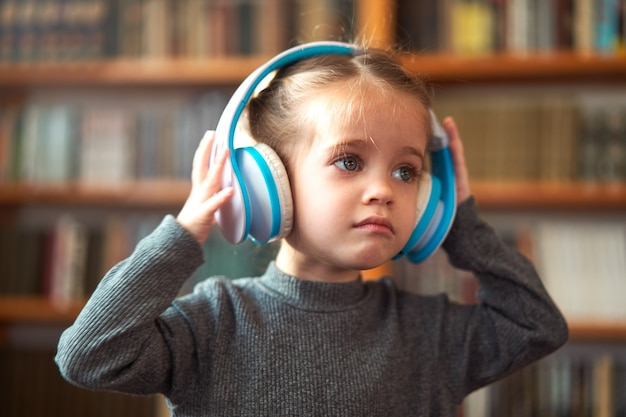 Linda garotinha caucasiana com grandes fones de ouvido brancos ouve música no interior