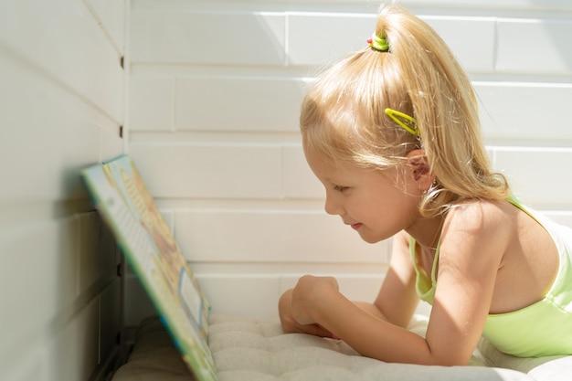 Linda garotinha caucasiana lendo um livro