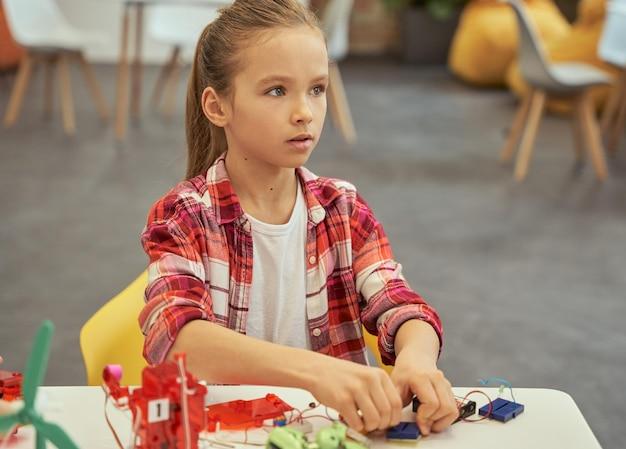 Linda garotinha caucasiana olhando para longe enquanto monta um kit de brinquedo eletrônico sentado