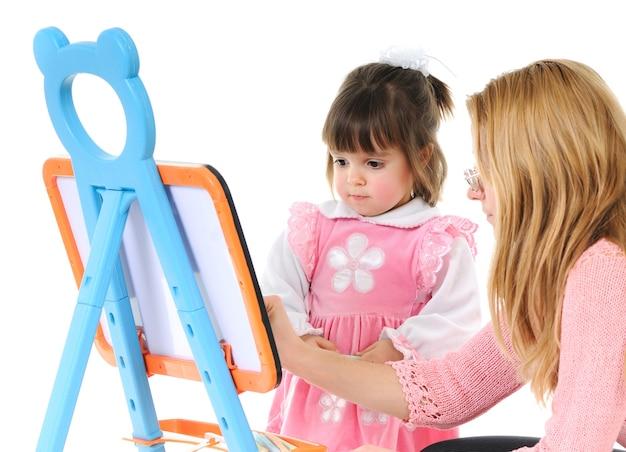 Linda garotinha com a mãe desenhando na lousa