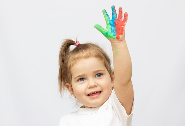 Linda garotinha com as mãos na tinta
