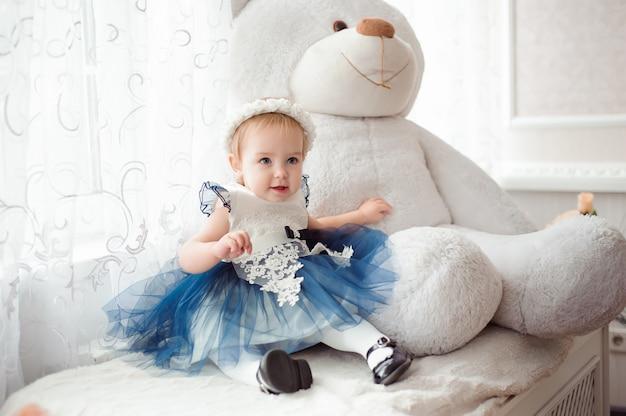 Linda garotinha com brinquedo sorrindo para a câmera