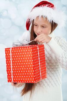 Linda garotinha com caixa de presente em fundo brilhante