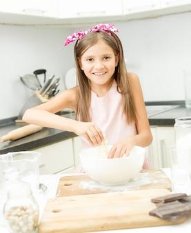 Linda garotinha com laço rosa no cabelo fazendo massa em uma tigela grande
