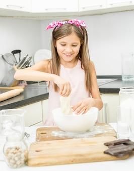 Linda garotinha com laço rosa no cabelo fazendo massa na cozinha