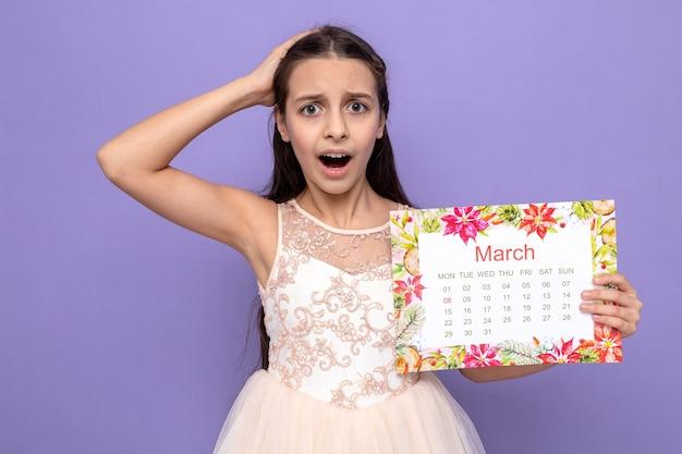Linda garotinha com medo de colocar a mão na cabeça no dia da mulher feliz segurando o calendário isolado na parede azul
