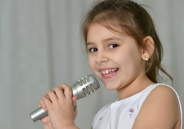 Linda garotinha com microfone em casa