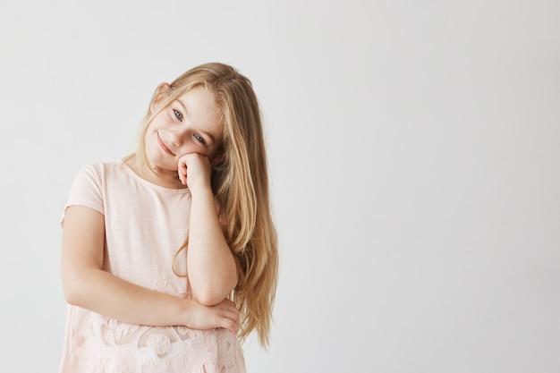 Linda garotinha com olhos azuis e cabelos claros em um lindo vestido rosa sorri e segurando a bochecha com a mão.