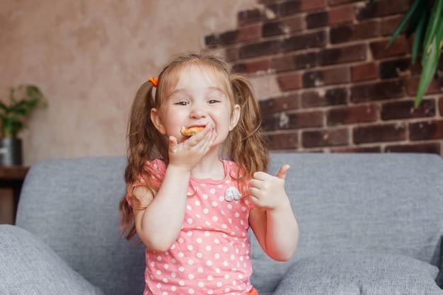 Linda garotinha comendo pizza em casa e levantando o polegar