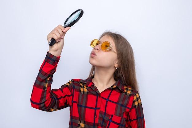 Linda garotinha confusa de camisa vermelha e óculos, segurando e olhando para a lupa