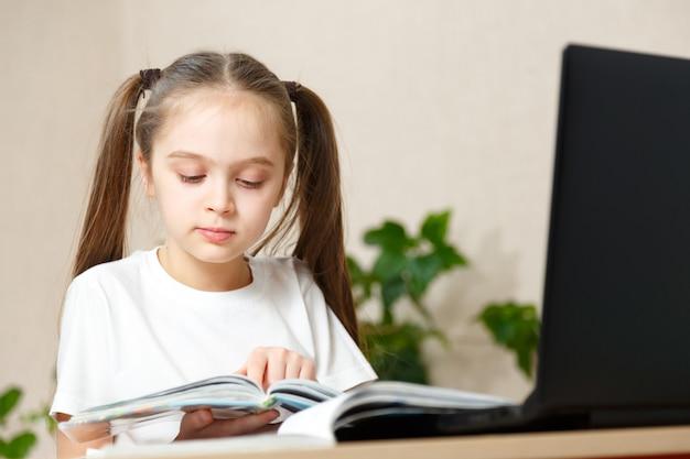 Linda garotinha da escola trabalhando em casa no quarto dela com um laptop e notas de aula, estudando em um