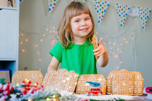 Linda garotinha de 3 anos comendo a casa de biscoitos de gengibre, brincando com a cidade de biscoitos de gengibre. foco seletivo na garota.