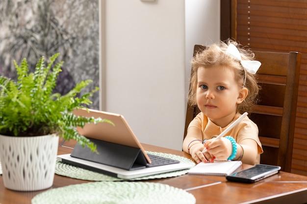 Linda garotinha de 3 anos de idade com cabelo encaracolado está sentada à mesa e recebendo aulas de idiomas educacionais no tablet. conceito de educação infantil