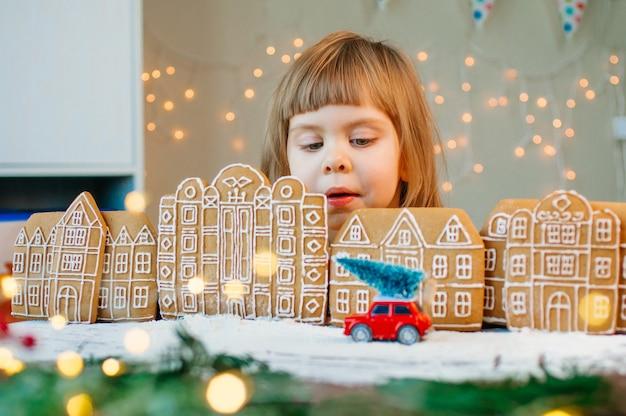Linda garotinha de 3 anos olhando para o brinquedo do carro com a árvore de natal na cidade de biscoitos de gengibre. foco seletivo na garota.