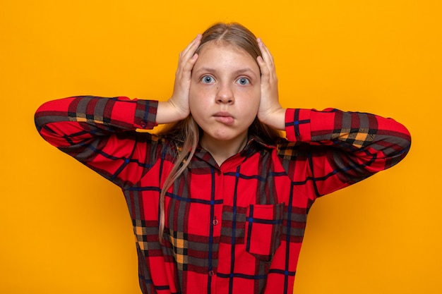 Linda garotinha de camisa vermelha com medo agarrou a cabeça