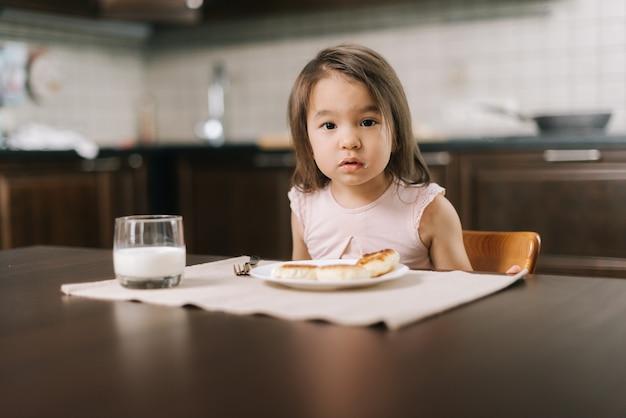 Linda garotinha de dois anos esperando a refeição para começar a olhar para a câmera