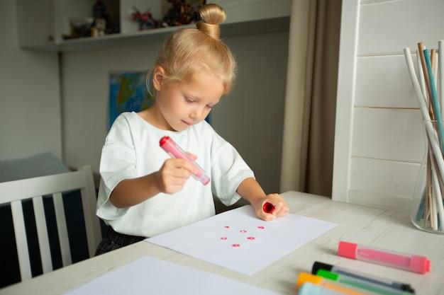 Linda garotinha desenha à mesa em casa Foto Premium