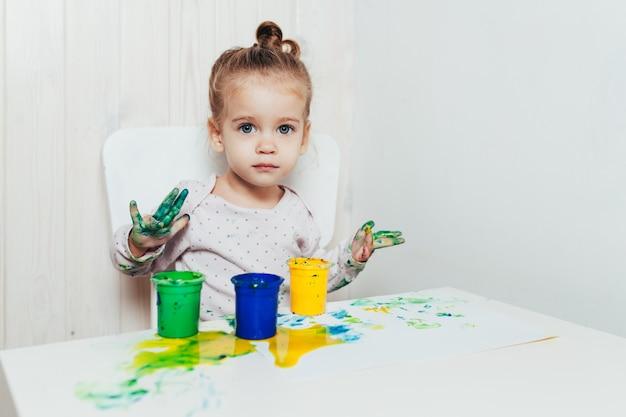 Linda garotinha desenha com tintas de dedo em uma folha de papel branca