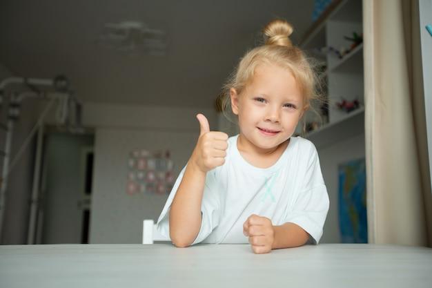 Linda garotinha em casa na mesa com gesto de mão Foto Premium