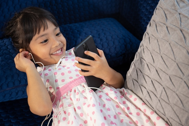 Linda garotinha em fones de ouvido usando o smartphone em um sofá