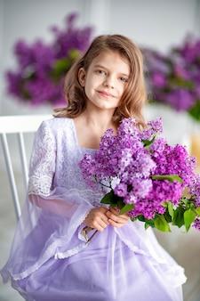 Linda garotinha em idade pré-escolar em um vestido delicado sentada em um balanço decorado com flores lilás