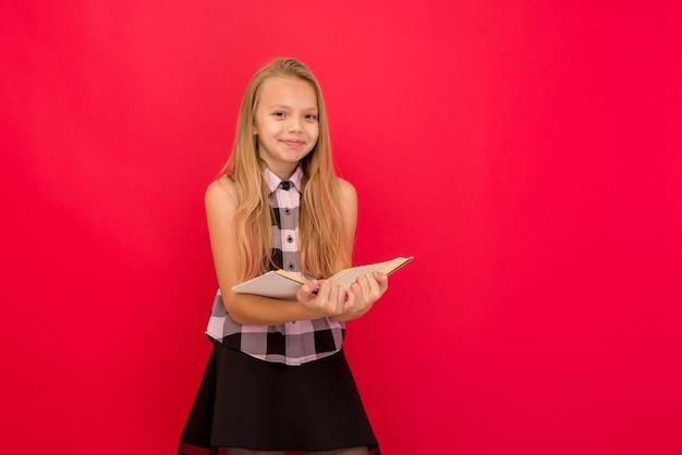 Linda garotinha em pé e lendo um livro sobre o vermelho -