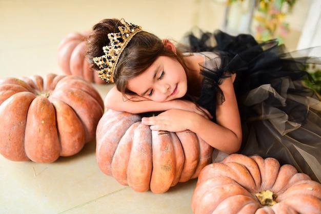Linda garotinha em preto noite gawn senta-se sobre os pampkins em um estúdio