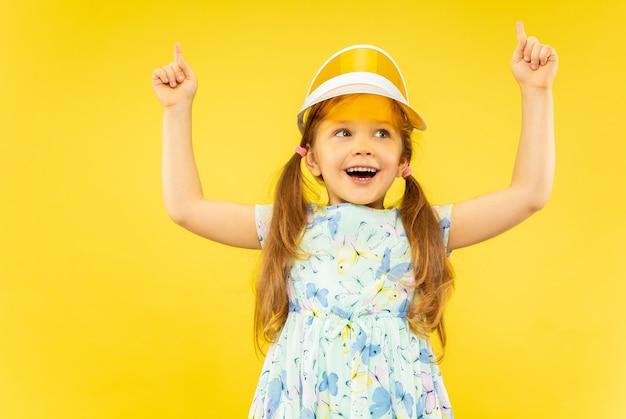 Linda garotinha emocional isolada. retrato de criança feliz weard em vestido e boné laranja apontando para cima. conceito de verão, emoções humanas, infância.