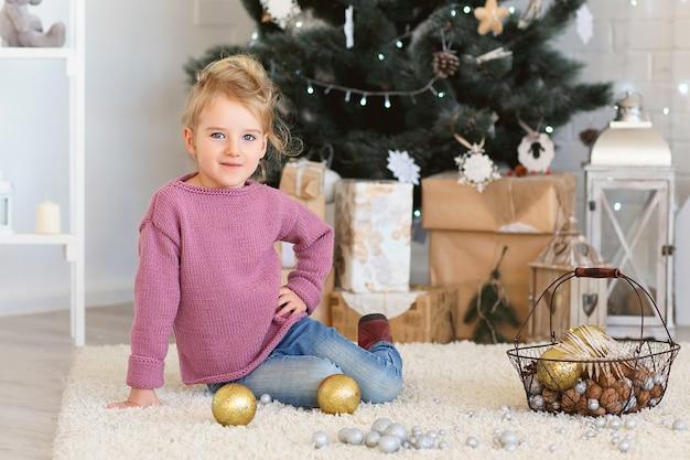 Linda garotinha esperando por um milagre nas decorações de natal