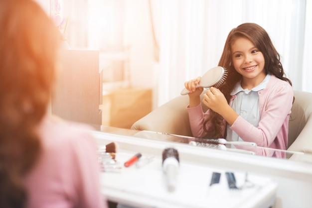 Linda garotinha está penteando o cabelo no salão de beleza.