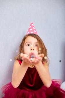 Linda garotinha explode confetes multicoloridos, se divertindo na festa de aniversário em casa. criança feliz aniversário.