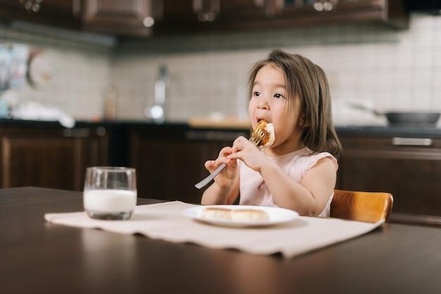 Linda garotinha faminta comendo um saboroso cheesecake com garfo no almoço