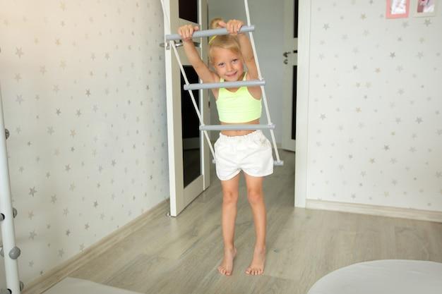 Linda garotinha fazendo esportes em casa