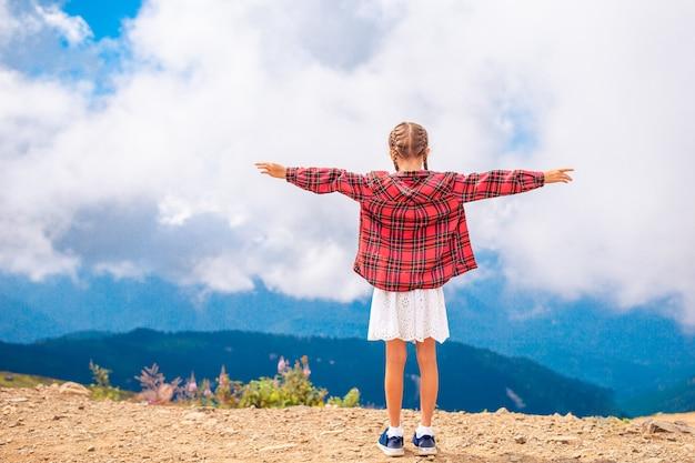 Linda garotinha feliz nas montanhas no fundo do nevoeiro