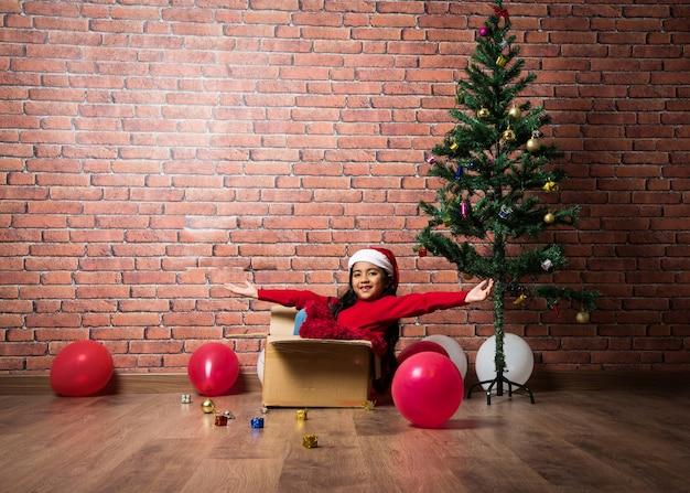 Linda garotinha indiana asiática comemorando o natal enquanto está sentada em uma caixa de papelão contra a parede de tijolo vermelho, interior