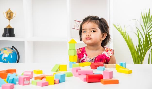 Linda garotinha indiana asiática curtindo enquanto brinca com brinquedos ou blocos, sentada à mesa
