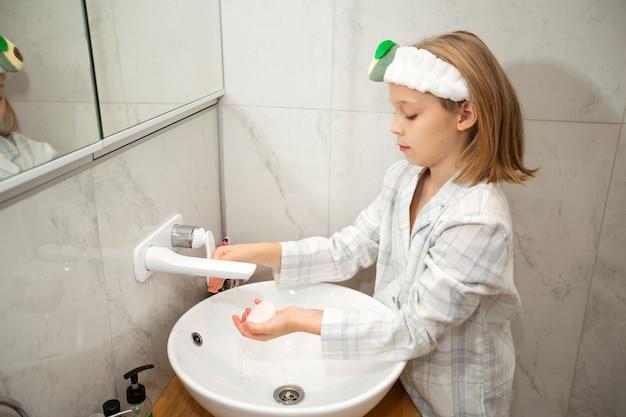 Linda garotinha lavando as mãos no banheiro