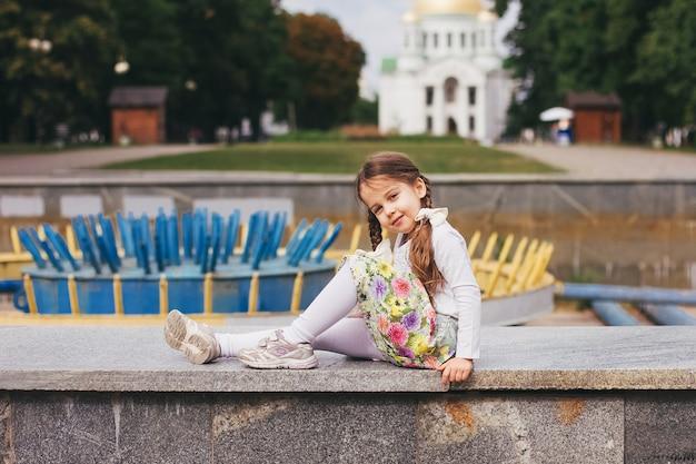 Linda garotinha linda com roupa branca brilhante, posando ao ar livre no parque.