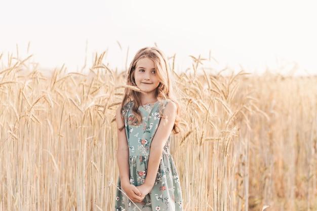 Linda garotinha loira com cabelo comprido caminhando por um campo de trigo