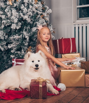 Linda garotinha loira princesa está sorrindo com um cachorro samoieda engraçado branco pela árvore de ano novo com caixas de presente.