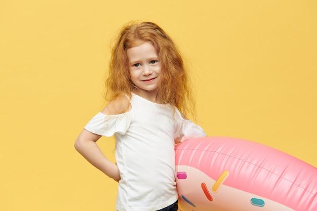 Linda garotinha posando isolada segurando um tubo inflável rosa debaixo do braço indo para a praia, tendo uma expressão facial feliz