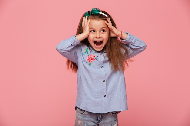 Linda garotinha reagindo emocionalmente agarrando a cabeça com as duas mãos, sendo encantada e chocada
