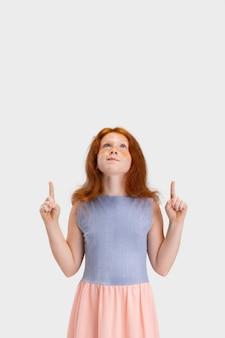 Linda garotinha ruiva com roupa casual posando isolado no fundo branco do estúdio.