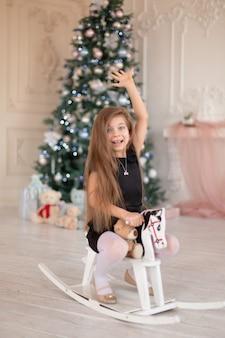 Linda garotinha se alegra com o cavalo de balanço de madeira, um presente de natal do papai noel.