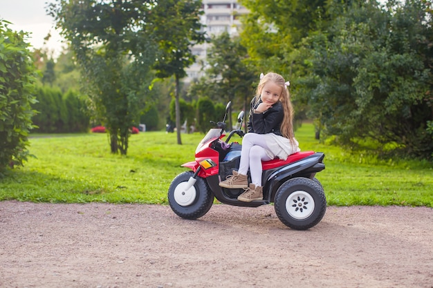 Linda garotinha se divertindo em sua bicicleta de brinquedo no parque verde