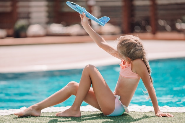 Linda garotinha se divertindo perto de uma piscina ao ar livre