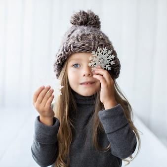 Linda garotinha segurando flocos de neve