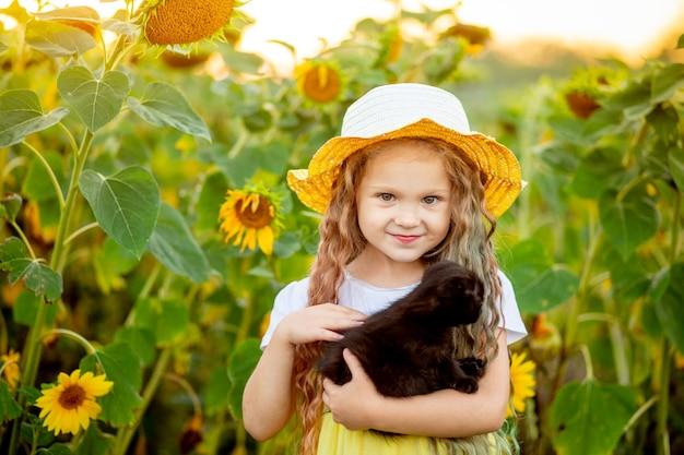 Linda garotinha segurando um gatinho preto em um campo com girassóis no verão