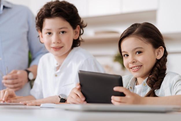 Linda garotinha sentada ao lado do irmão no balcão da cozinha e segurando um tablet enquanto os dois olham para a frente e sorriem